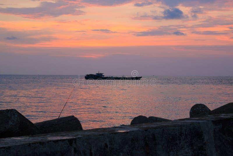 Живописный заход солнца около моря с кораблем, утесами, горизонтом, рыболовной удочкой и оранжевыми облаками Phu Quoc, Вьетнам стоковые фото