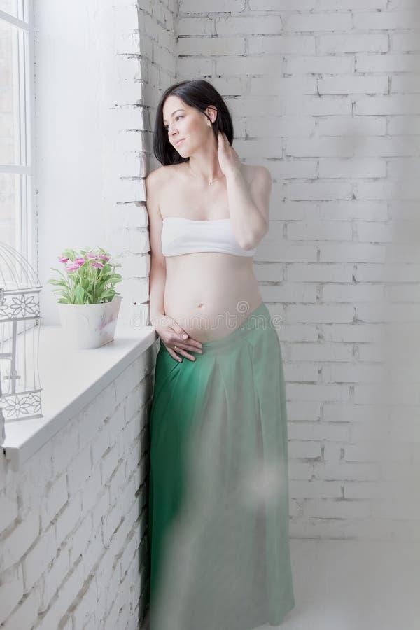 живот обнимая ее беременную женщину стоковое изображение