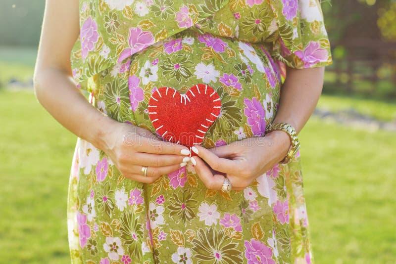 Живот символа беременной женщины и сердца outdoors стоковое фото rf