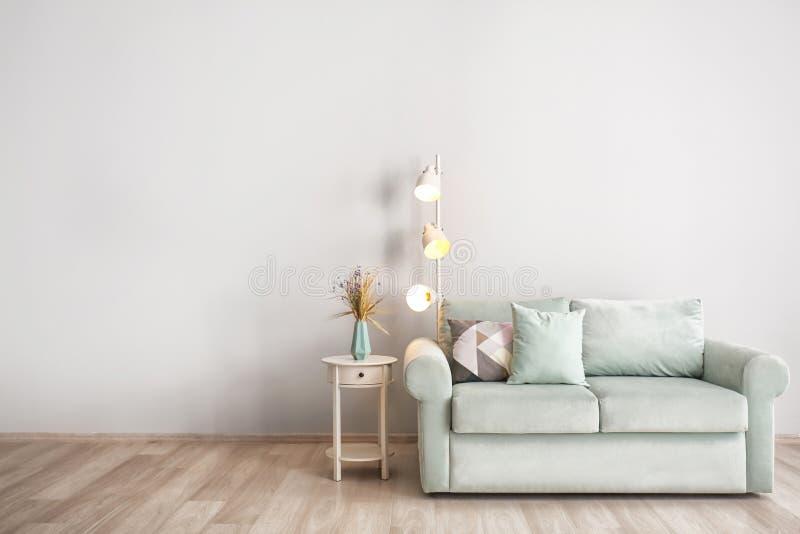 Живущая комната с софой, лампой пола и таблицей около светлой стены стоковые изображения rf