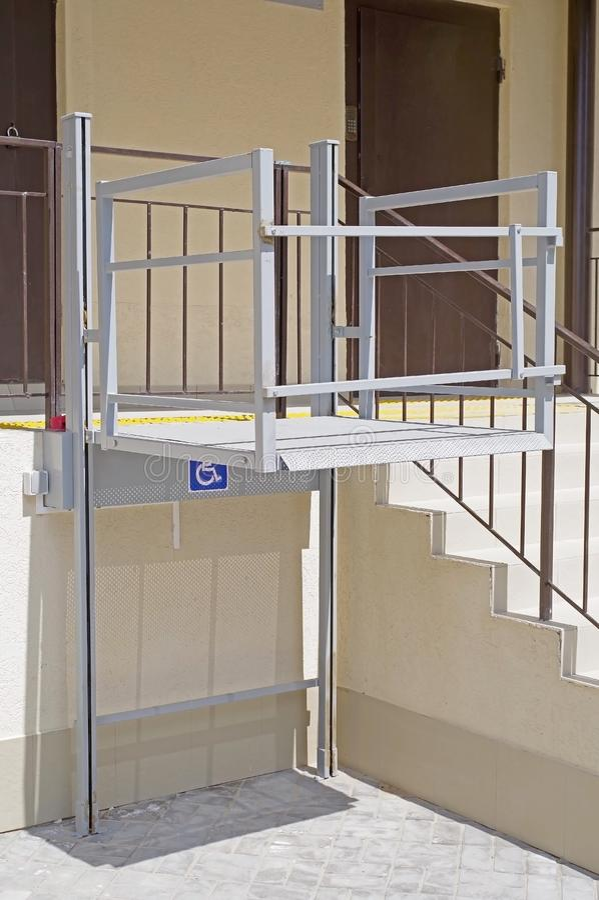 Живя вход дома оборудованный с поднимаясь платформой для человеков в инвалидной коляске стоковые изображения
