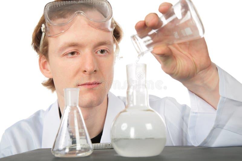 жидкость склянки химика льет стоковое фото rf