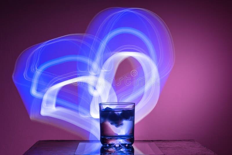 Жидкость с льдом в стекле на отражательной поверхности на рыжеватой предпосылке стоковые фотографии rf
