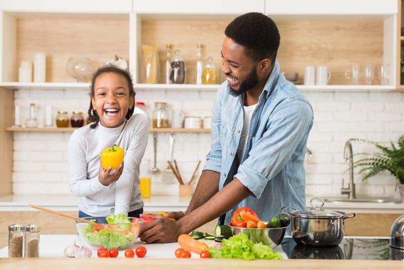 Жизнерадостная афро девушка держа перец пока помогающ отцу варя обедающий стоковые изображения rf