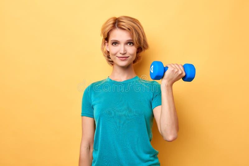Жизнерадостная белокурая женщина держа весы изолированный на желтой предпосылке стоковая фотография