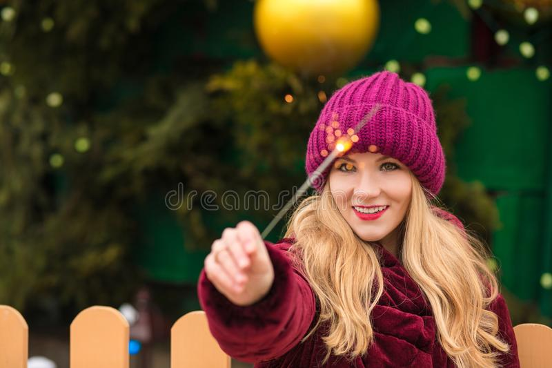 Жизнерадостная белокурая женщина одела в ультрамодном одеянии, держа sparkli стоковое изображение