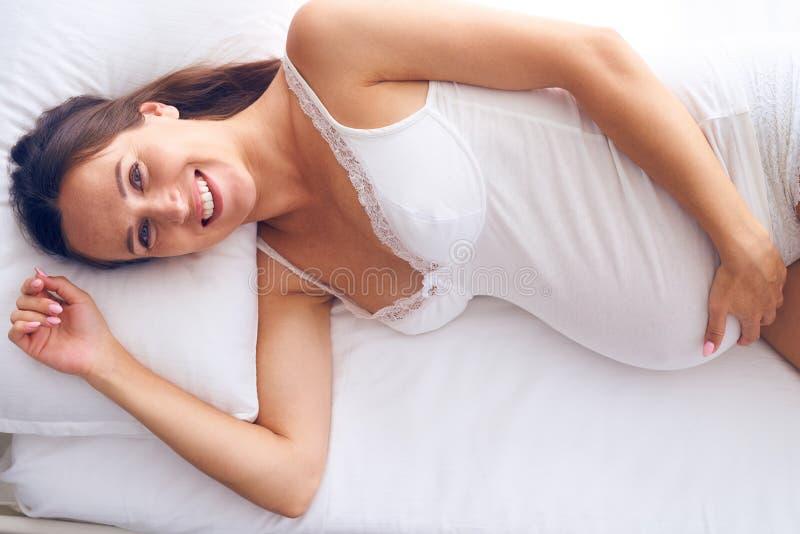 Жизнерадостная беременная женщина лежа на белом листе в кровати стоковые фотографии rf