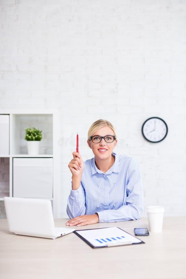 Жизнерадостная бизнес-леди сидя в офисе и показывая знак идеи - космос экземпляра над белой стеной стоковые фото