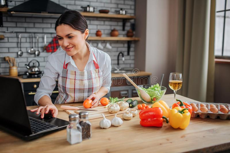 Жизнерадостная взрослая женщина сидит на таблице в кухне Она печатая на клавиатуре и взгляде на экране Еда повара женщины стоковая фотография