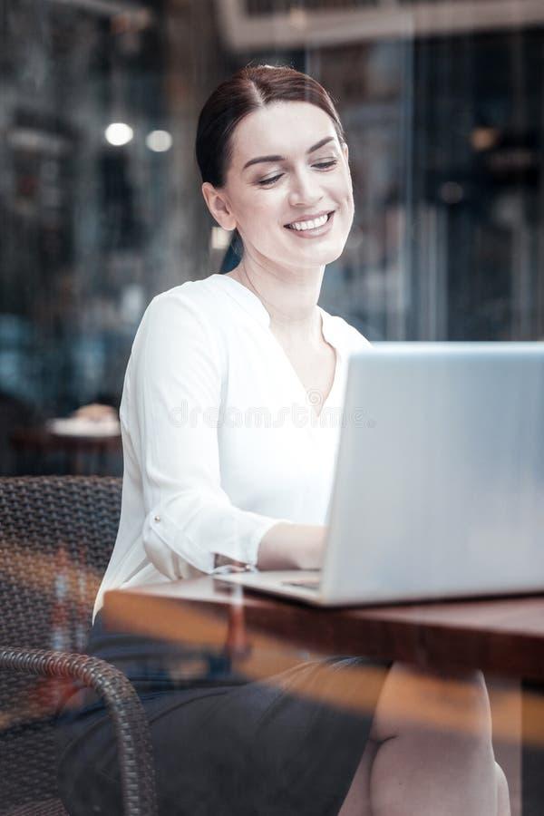 Жизнерадостная дама смотря экран ее компьютера стоковые изображения