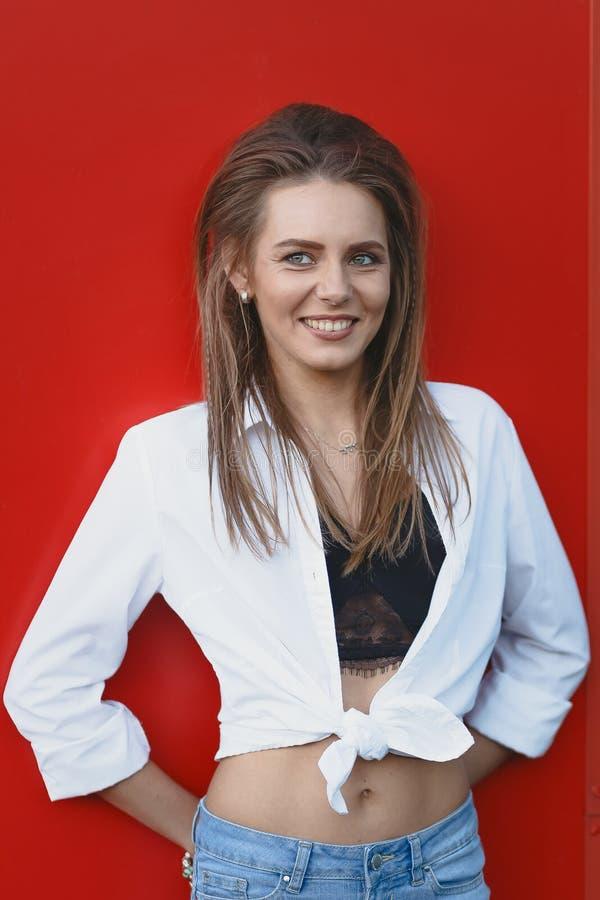 Жизнерадостная девушка в белых рубашке и джинсах на красной предпосылке стоковое фото rf