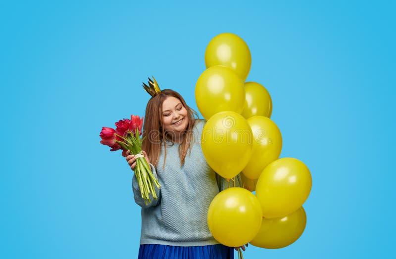 Жизнерадостная добавочная женщина размера с цветками и воздушными шарами стоковые изображения