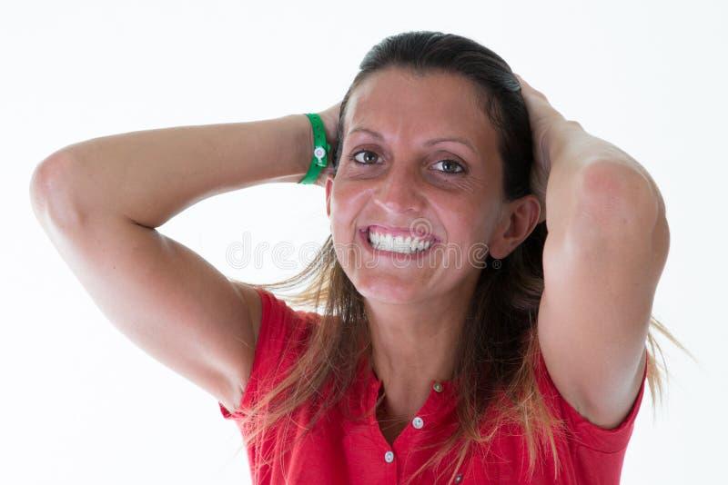 Жизнерадостная женщина брюнета с руками на волосах в белой предпосылке стоковое изображение rf