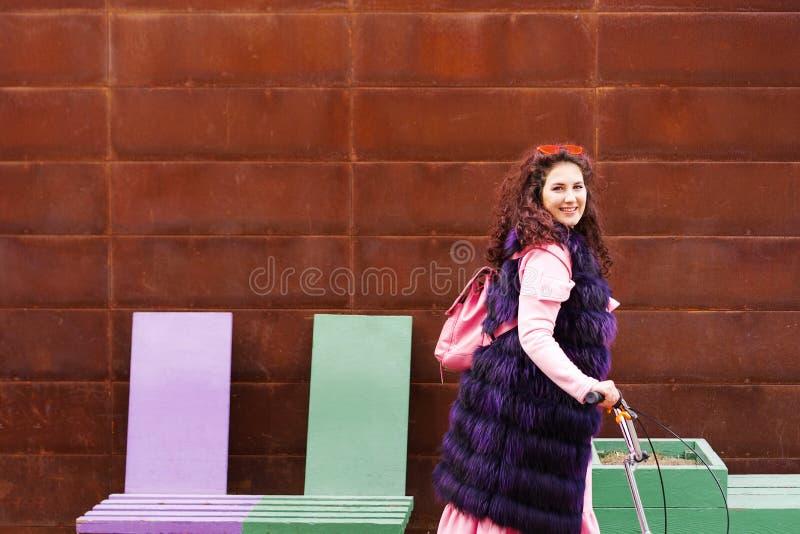 Жизнерадостная женщина в розовом платье и пурпурной накидке меха ехат стоковое изображение