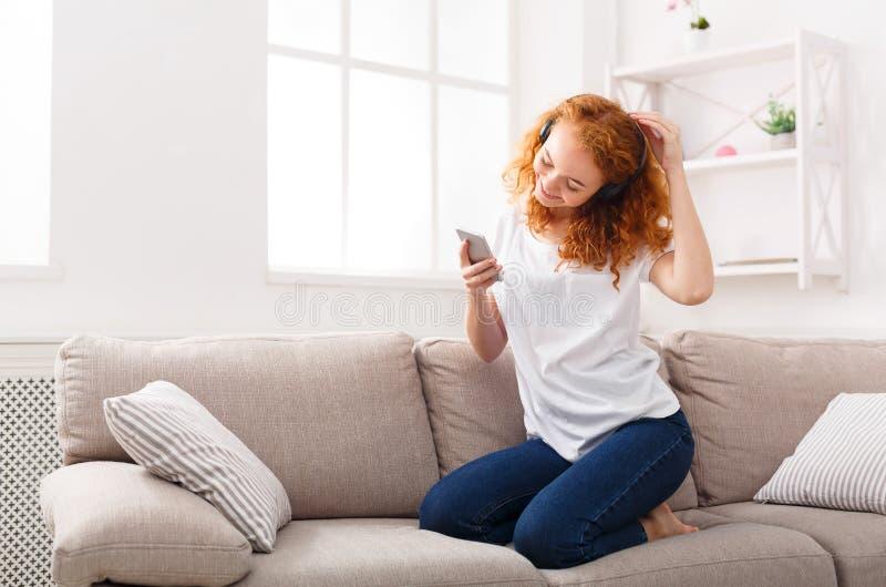Жизнерадостная женщина наслаждаясь ее любимой песней в наушниках стоковые фотографии rf