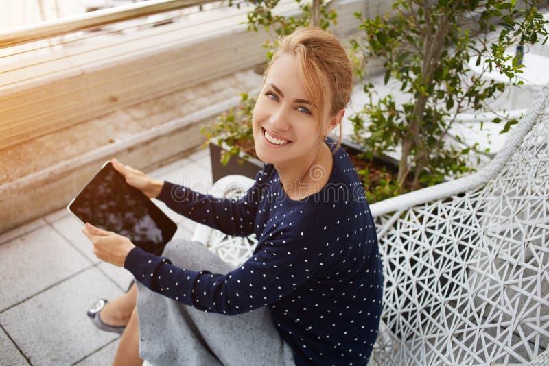 Жизнерадостная женщина с сенсорной панелью в руках представляет для камеры стоковое фото