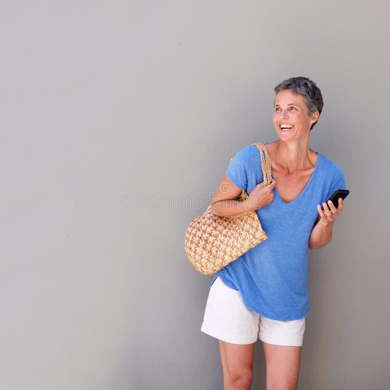 Жизнерадостная женщина с сумкой и мобильным телефоном стоковое фото rf