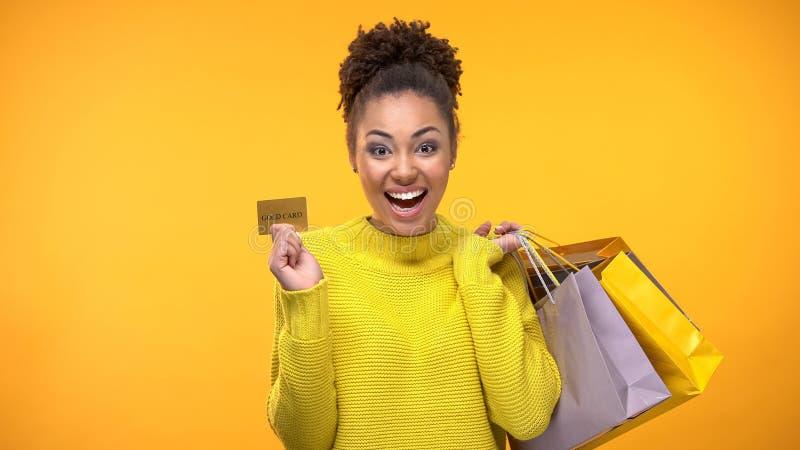 Жизнерадостная женщина с хозяйственными сумками и золотой кредитной карточкой, богатым обслуживанием клиента стоковая фотография rf