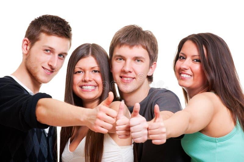 жизнерадостная компания показывая большие пальцы руки вверх стоковое фото