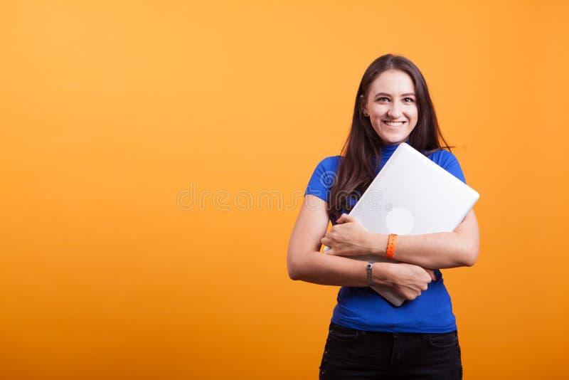 Жизнерадостная красивая молодая женщина держа компьтер-книжку стоковые фотографии rf
