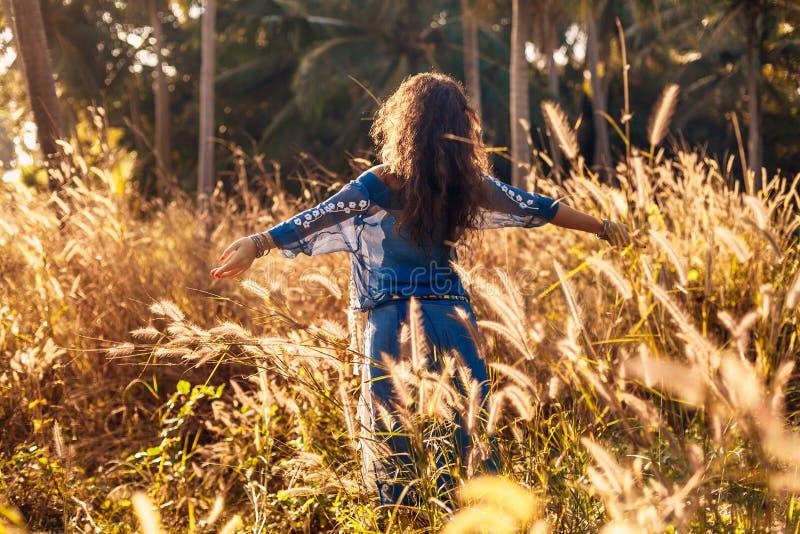 Жизнерадостная красивая молодая женщина имея потеху на поле на заходе солнца стоковые изображения