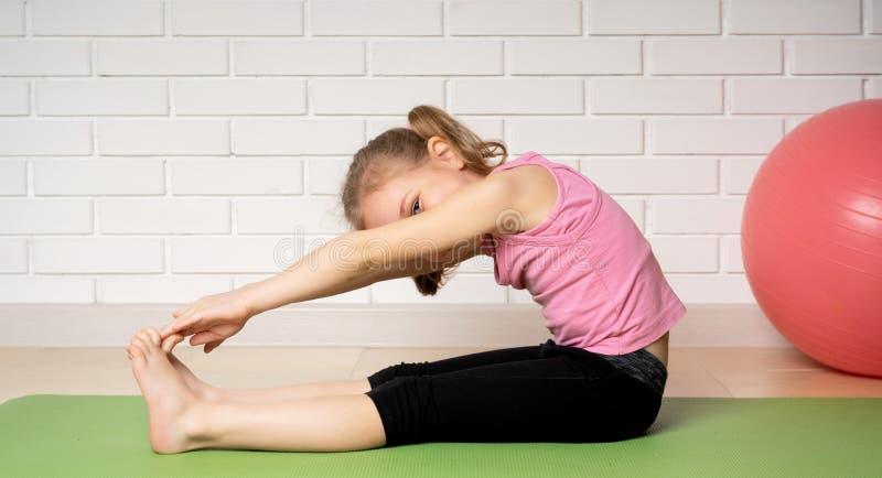 Жизнерадостная маленькая девочка делая тренировки спорт на циновке дома, спорт детей и йоге стоковые фотографии rf