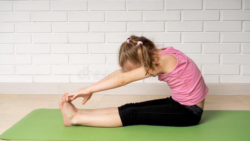 Жизнерадостная маленькая девочка делая тренировки спорт на циновке дома, спорт детей и йоге стоковая фотография