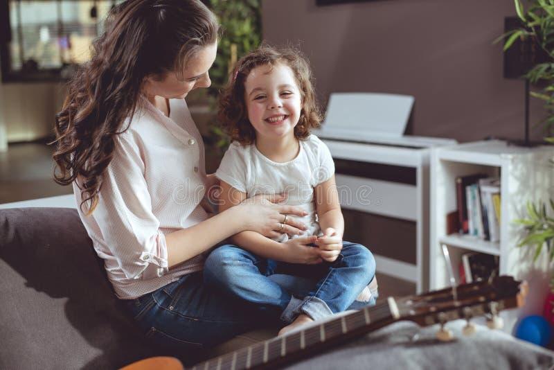 Жизнерадостная мать и дочь ослабляя в живущей комнате стоковые изображения