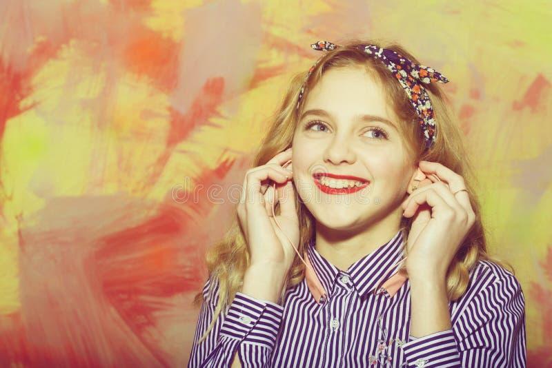 Жизнерадостная милая девушка слушает музыку с наушниками стоковые фото