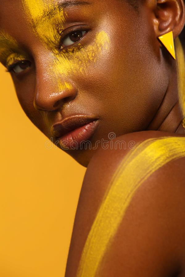 Жизнерадостная молодая африканская женщина с желтым составом весны на ей глаза Женский модельный смеяться над против желтого лета стоковое фото rf