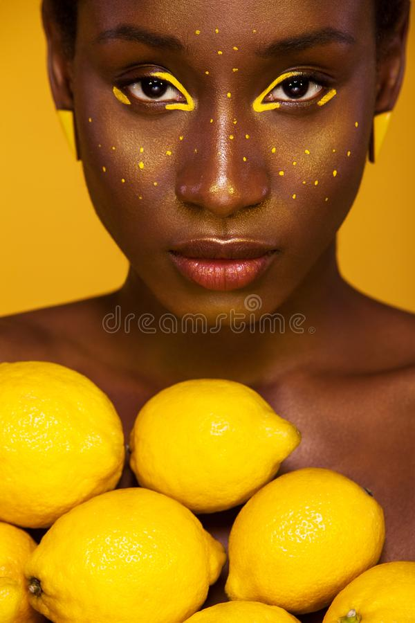 Жизнерадостная молодая африканская женщина с желтым составом на ей глаза Женская модель против желтой предпосылки с желтыми лимон стоковая фотография rf