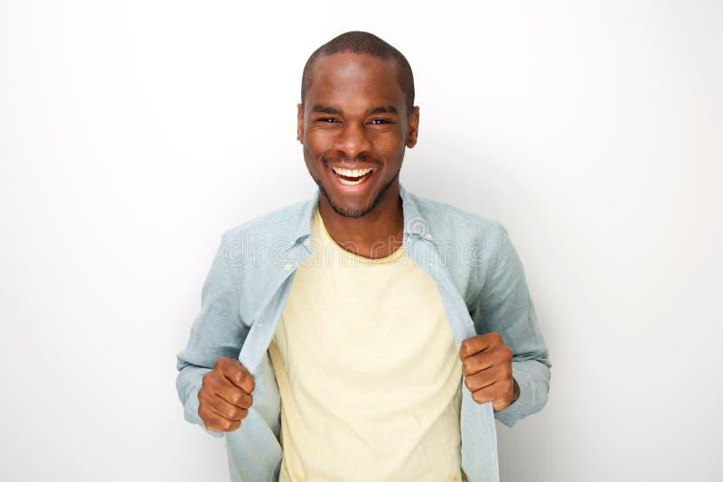 Жизнерадостная молодая Афро-американская рубашка удерживания человека открытая белой предпосылкой стоковое изображение