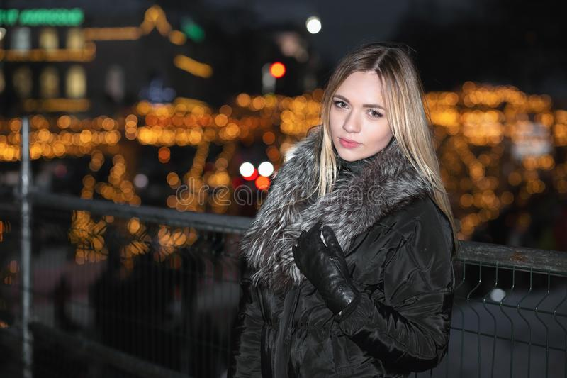 Жизнерадостная молодая блондинка в черный представлять одежд стоковое изображение