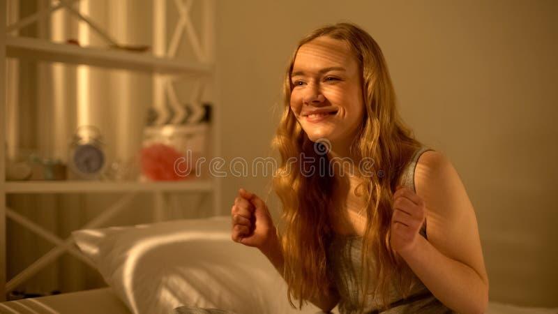 Жизнерадостная молодая дама сидя на кровати, весьма счастливой о получать хорошие новости стоковая фотография rf
