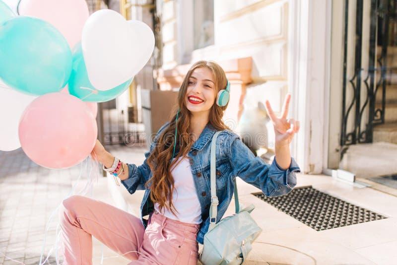 Жизнерадостная молодая дама с ежедневным макияжем представляя снаружи с воздушными шарами и знаком мира Привлекательный усмехаясь стоковое фото