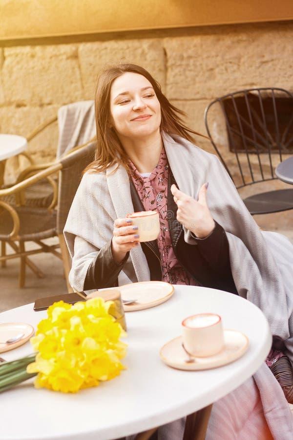 Жизнерадостная молодая женщина в кофе кафа улицы выпивая стоковое изображение rf