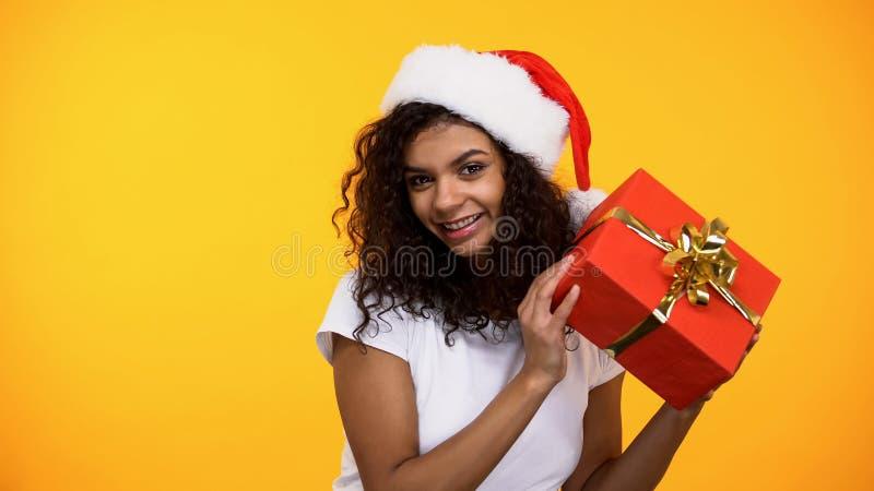 Жизнерадостная молодая женщина в шляпе Санта Клауса держа камеру присутствующей коробки усмехаясь стоковое фото
