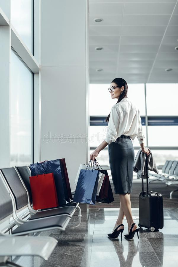 Жизнерадостная молодая женщина идет на отключение самолетом стоковое изображение rf