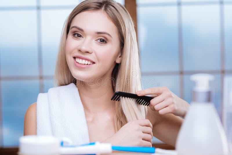 Жизнерадостная молодая женщина расчесывая ее волосы стоковые изображения rf