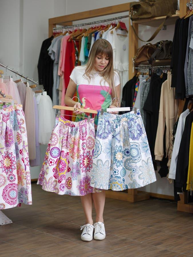 Жизнерадостная молодая женщина стоя в магазине одежды и выбирая красочная юбка Shopaholic на запачканное стоковая фотография rf