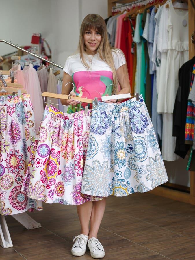 Жизнерадостная молодая женщина стоя в магазине одежды и выбирая красочная юбка Shopaholic на запачканное стоковые изображения rf