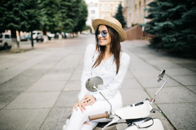 Жизнерадостная молодая женщина управляя самокатом в улице городка стоковое фото rf