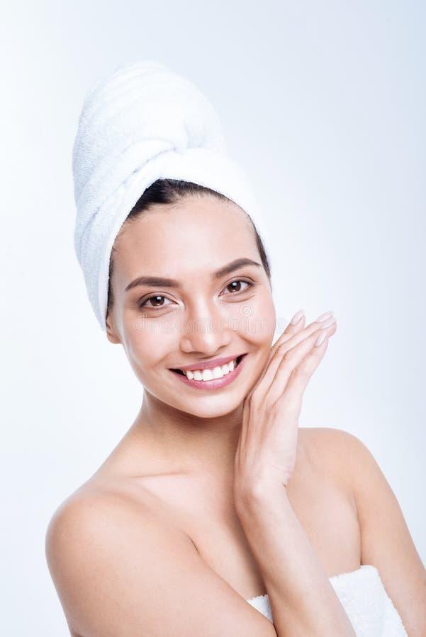 Жизнерадостная молодая женщина усмехаясь пока представляющ в тюрбане полотенца стоковые фото