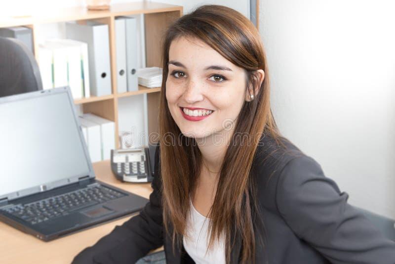 жизнерадостная молодая коммерсантка работая на компьтер-книжке и усмехаясь пока сидящ на ее офисе стола стоковые фотографии rf