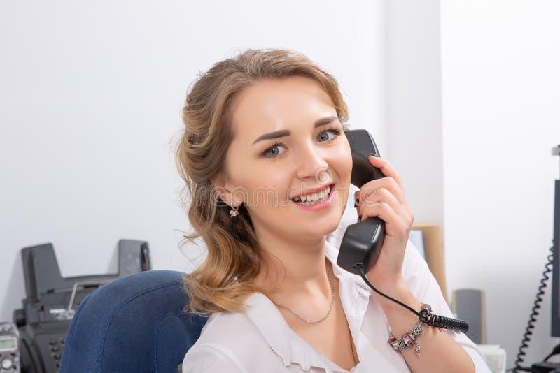 Жизнерадостная молодая красивая женщина italking по телефону и смотря камеру с улыбкой пока сидящ на ее месте службы стоковое фото rf