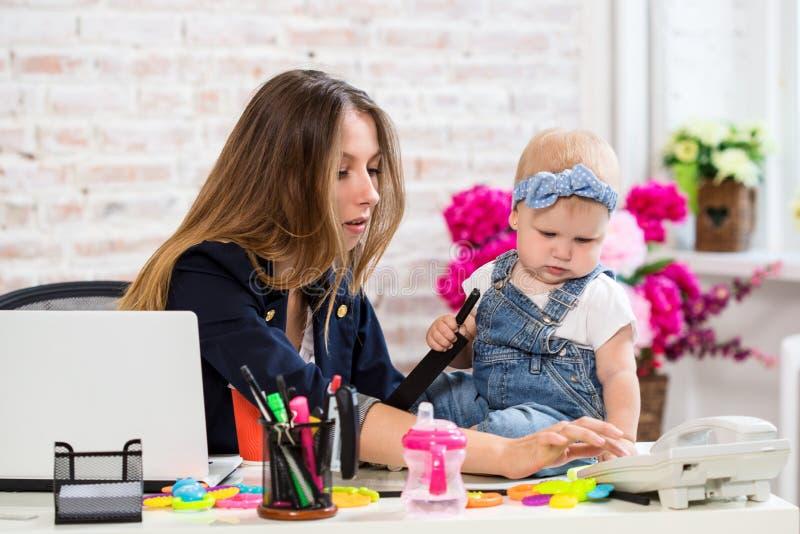 Жизнерадостная молодая красивая коммерсантка смотря телефон пока сидящ на ее месте службы с ее маленькой дочерью стоковое фото