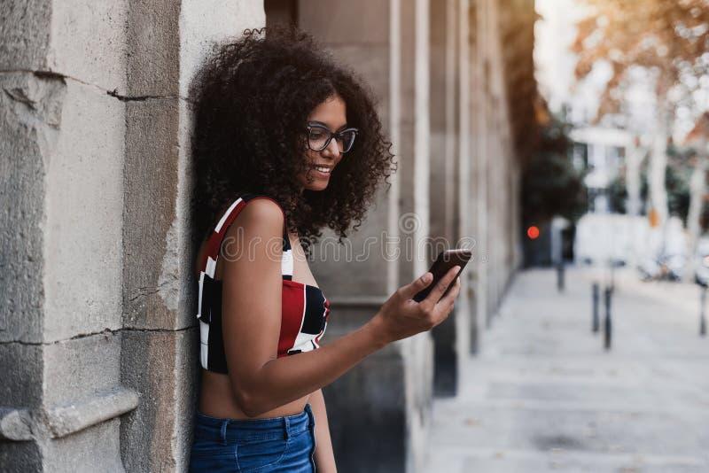 Жизнерадостная молодая курчавая женщина на улице с мобильным телефоном стоковые изображения