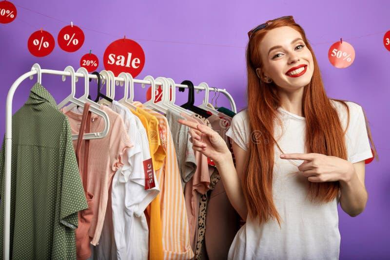 Жизнерадостная молодая очаровательная девушка указывая на одежды стоковое изображение