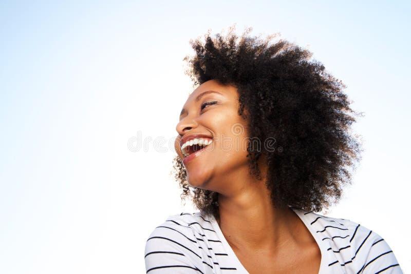 Жизнерадостная молодая чернокожая женщина смеясь над outdoors против яркого неба стоковое фото rf