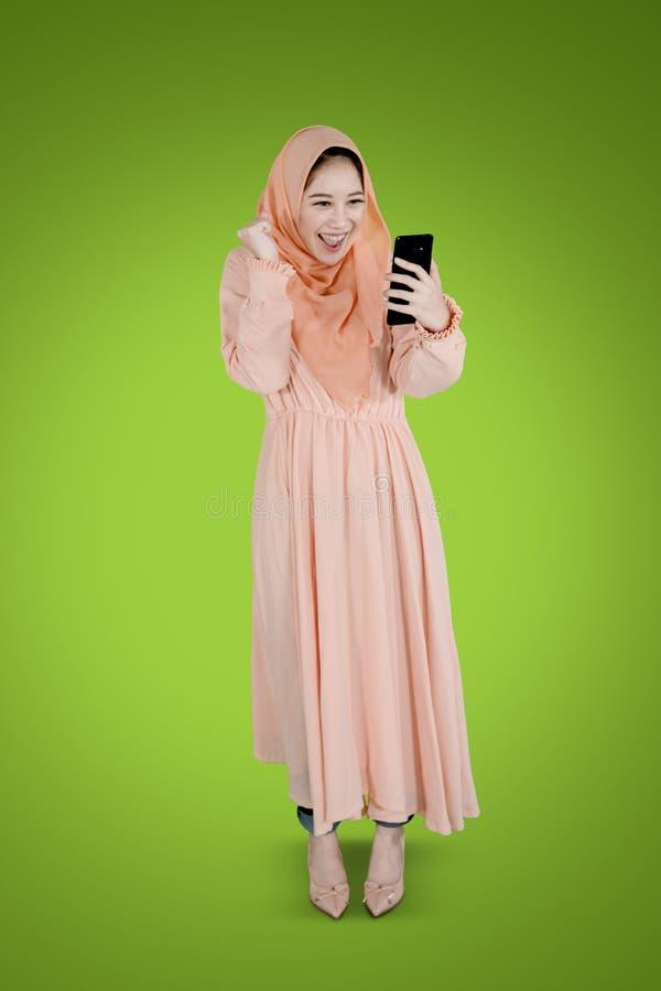 Жизнерадостная мусульманская женщина с телефоном на студии стоковое фото